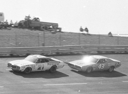 David Pearson (21) makes a move around the slower car of Richard Petty.