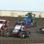 Shane Cottle (5c) and Zach Daum (5d) lead a pack of midgets at Gas City (Ind.) I-69 Speedway Wednesday during the Indiana Midget Week opener. (Gary Gasper Photo)