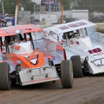Tight dirt track action qualifying at New York's Fonda Speedway as Ronnie Johnson (2rj) races with A.J. Romano in the modified division. (Harry Cella Photo)