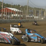 Competitors for Saturday's co-sanctioned Badger/POWRi Midget Series feature, kick up a little mud at Wisconsin's Wilmot Raceway. (Brett Moist photo)