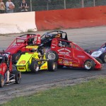 In the first heat race, Tom Schnabel (red car, center) got tangled up with several others during STARS/USAC D1 midget competition at Grundy County Speedway in Illinois. (Phil Rider photo)