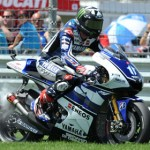 Ben Spies pulls his broken motorcycle off the track during Sunday's MotoGP event at Indianapolis Motor Speedway. (David E. Heithaus Photo)