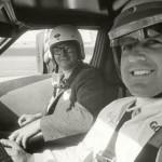 Chris Economaki shares a seat alongside legendary racer A.J. Foyt. (NSSN Archives Photo)