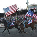 Horse riders wave American flags during pre-race ceremonies ahead of the World 100 at Eldora Speedway Saturday. (Julia Johnson Photo)