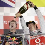 Jenson Button pours champagne on Singapore Grand Prix winner Sebastian Vettel Sunday at the Marina Bay Street Circuit. (Steve Etherington Photo)