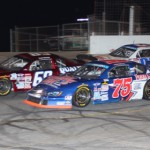 Caleb Holman (75) and Allen Purkhiser (68) lead the Rev-Oil Pro Cup Series field into turn one during a restart Saturday at Hickory (N.C.) Motor Speedway. (Adam Fenwick/AKFPhotos.com Photo)