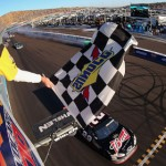 Kevin Harvick crosses the finish line to win Sunday's AdvoCare 500 at Phoenix Int'l Raceway as a crash takes place behind him. (NASCAR Photo)