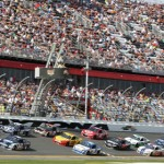A large pack of cars flashes under the start-finish line during the first Budweiser Duel at Daytona Int'l Speedway on Thursday. (HHP/Christa L. Thomas Photo)