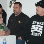 11-year-old driver Michael Lake (left) and NeSmith Chevrolet Dirt Late Model Series Director Mike Vaughn (center) listen to Bubba Raceway Park owner Bubba the Love Sponge during the drivers meeting Friday. (Al Steinberg Photo)