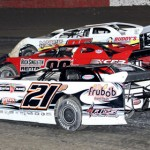 Josh Peacock (21p), Rick Singleton (99*) and Devin Dixon battle for position Saturday during Fastrak Late Model action at East Bay Raceway Park in Florida. (R.E. Wing Photo)