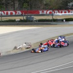 Tristan Vautier (55) leads a pack of cars through a turn at Barber Motorsports Park during Sunday's IZOD IndyCar Series race. (IndyCar Photo)