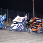 The Lucas Oil American Sprint Car Series field salutes the fans by going four-wide Friday evening at Golden Triangle Raceway Park. (RonSkinnerPhotos.com Photo)
