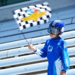 A young fan waves an Indianapolis Motor Speedway checkered flag during Monday's practice session. (IndyCar Photo)