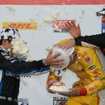 Ryan Hunter-Reay, Helio Castroneves and Will Power toss Wisconsin cream puffs at each other on the podium after Saturday's IZOD IndyCar Series race at The Milwaukee Mile. (Al Steinberg Photo)