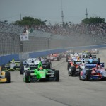 The IZOD IndyCar Series field flows into turn one at the start of June's race at The Milwaukee Mile in West Allis, Wis. Next year all Indy cars will be powered by twin-turbocharged engines. (Al Steinberg Photo)