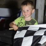 Rusty Schlenk's son holds the checkered flag for his dad in victory lane after Rusty won the UMP late model feature at Ohio's Attica Raceway Park. (Action photo)