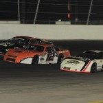 Rip Michels (12) takes the lead from Jason Patison (88) and  Andre Prescott during late model competition at Irwindale (Calif.) Events Center. (Marv Keller photo)