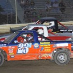 Brad Mitten (23m), Willie Keegan (51p) and Brandon Stuckey race three wide during dirt truck competition at Attica (Ohio) Raceway Park.
