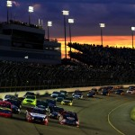 The sun sets in the background as the NASCAR Camping World Truck Series field heads for turn one at Iowa Speedway. (NASCAR Photo)
