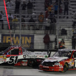 Kyle Busch (51) crosses the finish line to win Wednesday's NASCAR Camping World Truck Series race at Bristol (Tenn.) Motor Speedway as Timothy Peters begins to spin into the inside wall. (NASCAR Photo)