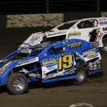 Tim Karrick and Ryan Gustin (19r) race for the lead during modified competition at Lakeside Speedway in Kansas City, Kan. (Ivan Veldhuizen photo)