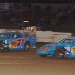 Brad DeYoung (7) and Don Stone (77) battle early in the IMOD feature at Plymouth (Ind.) Speedway. (Gary Gasper photo)