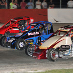 Midgets race three wide during the D'Arcy GMC Pavement Nationals at Grundy County Speedway. (Phil Rider photo)