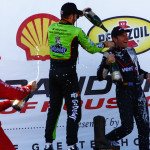 Will Power (right) gets a champagne bath from James Hinchcliffe after winning Sunday's IZOD IndyCar Series race in Houston, Texas. (IndyCar Photo)