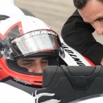 Juan Pablo Montoya looks over data after his laps in an IndyCar while Helio Castroneves looks on. (Al Steinberg Photo)