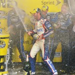 Jimmie Johnson celebrates with champagne in Victory Lane after winning the NASCAR Sprint Cup Series All-Star race at Charlotte Motor Speedway in Concord, North Carolina. (Photo by Drew Hallowell/Getty Images)