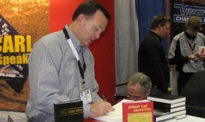 Dave Argabright signs copies of one of his books. (Linda Mansfield photo)