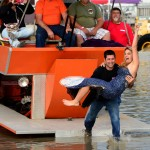 """To the crowd's delight, big feature winner Troy Ortega and Swamp Buggy Queen Jillian Sanchez go for the traditional Mudbath into the """"sippy hole."""" (Joe Secka/JMS Pro Photo)"""