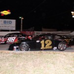 Garrett Campbell (12) races under Jody Measamer during Saturday's PASS South opener at Greenville (S.C.) Pickens Speedway. (LWPictures.com Photo)