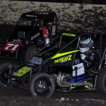 Brady Bacon (99) races alongside Christopher Bell during Saturday's Lucas Oil POWRi National Midget Series feature at Port City Speedway. (Boyd Adams Photo)