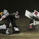 Greg Wilson (20w) avoids the spinning machine of Kerry Madsen during Friday's World of Outlaws STP Sprint Car Series event at Attica (Ohio) Raceway Park. (Julia Johnson Photo)