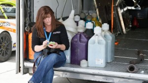 Karen Koch takes a little time to answer an email during a down moment at the track. (Doug Morrissey/SCCA photo)