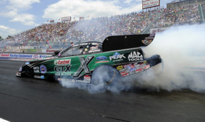 John Force performs a burnout Sunday at Summit Motorsports Park prior to collecting his 140th career NHRA Funny Car victory. (NHRA Photo)