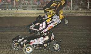 Greg Wilson (20) races under Sheldon Haudenschild Thursday at Waynesfield (Ohio) Raceway Park. (Mike Campbell photo)