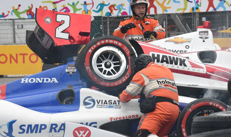 Safety workers work to remove Juan Pablo Montoya's entry in order to extricate Mikhail Aleshin from his IndyCar. Aleshin was unhurt in the crash. (Al Steinberg Photo)