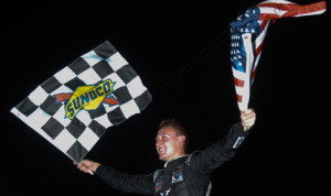 Daniel Hemric celebrates with the checkered flag and the American flag after winning Thursday's Firecracker 125 at Greenville Pickens Speedway. (Drew Hierwarter Photo)