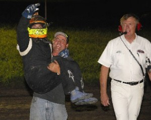 Isaac Schreurs, a 21-year-old paraplegic sprint car driver, gets carried out of his race car by his father Saturday night at Jefferson (S.D.) Park Speedway after he scored his first ASCS Midwest Region victory. (Doug Johnson Photo)