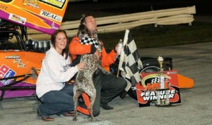 Trent Stephens gets a celebratory lick from his dog in victory lane after winning the Midwest Supermodified Ass'n event at Sandusky (Ohio) Speedway. (Todd Ridgeway Photo)
