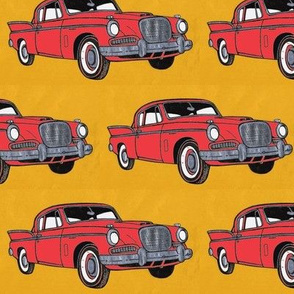 Big red finned 1957 Studebaker Hawk on gold background