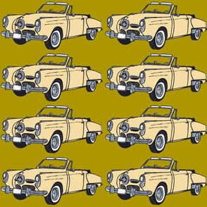 Cream 1950 Studebaker convertible on mustard green background