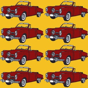 Red 1950 Studebaker convertible on yellow background
