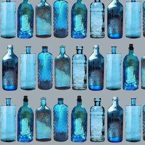 blue glass bottles on grey