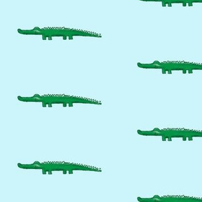 green crocodile with shadow, light aqua background