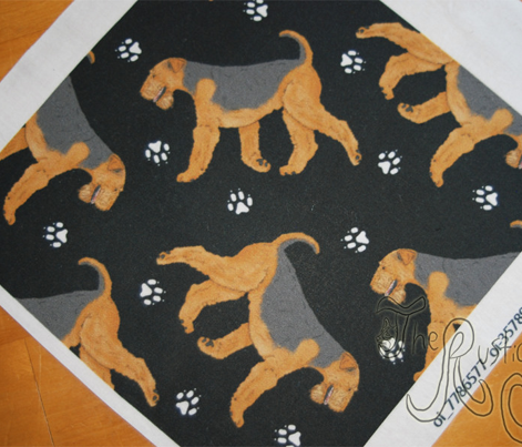 Trotting Airdale Terrier and paw prints - black