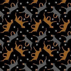Trotting Doberman Pinschers and paw prints - black