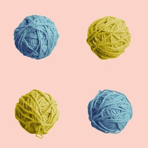 little blue and gold yarn balls on pink